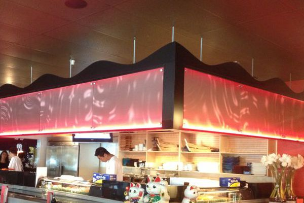 Illuminated Panels with Ripple Graphic Above Sushi Bar
